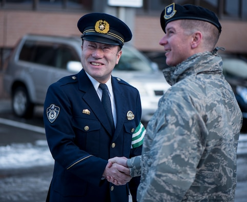 Nobuhiro Izumida, the Misawa City Police Station Chief shake hands with U.S. Air Force Maj. Patrick C. Gordon, the 35th Security Forces Squadron commander, after installing the first bi-lingual stop sign at an intersection in Misawa City, Japan, Feb. 15, 2018. While practically was the main objective in installing a bi-lingual stop sign, it can also be described as a great gesture of acceptance by the local community. (U.S. Air Force photo by Airman 1st Class Collette Brooks)