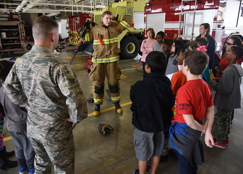 Airman 1st Class Kyle Tolle, 81st Infrastructure Division firefighter, demonstrates how to put on firefighter gear during Biloxi Career Exploration Day at the fire department Feb. 14, 2018, on Keesler Air Force Base, Mississippi. The school-aged children also toured the 334th Training Squadron, 335th TRS and the Trainer Development Center. (U.S. Air Force photo by Kemberly Groue)