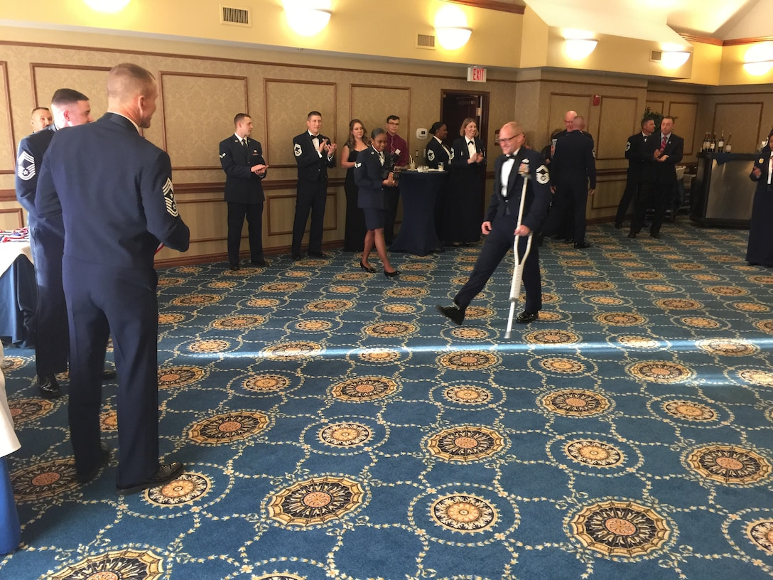 Then Senior Master Sgt. Chad Caden, the chief enlisted manager with the 633rd Civil Engineer Squadron at Joint Base Langley-Eustis, relies on a crutch during his Chief Induction ceremony in Hampton, Va., February 2017, nearly 2 months after receiving an amputation on his right leg due to a bone disease called Osteonecrosis. Osteonecrosis caused Caden's foot to lose blood flow and resulted in bone decay. This bone disease went undiagnosed for years while Caden experienced debilitating pain that significantly impacted his ability to work. (Courtesy  photo)