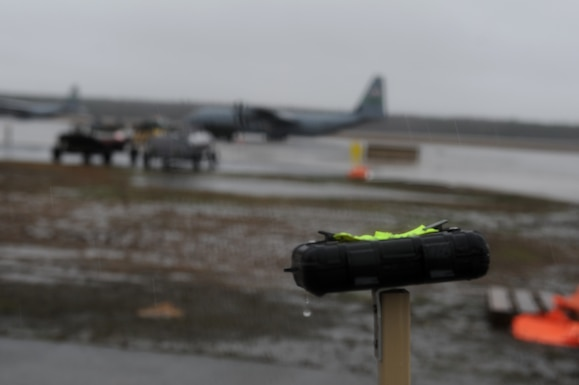 A rectangle photo with a black device in front a flightline with an aircraft.