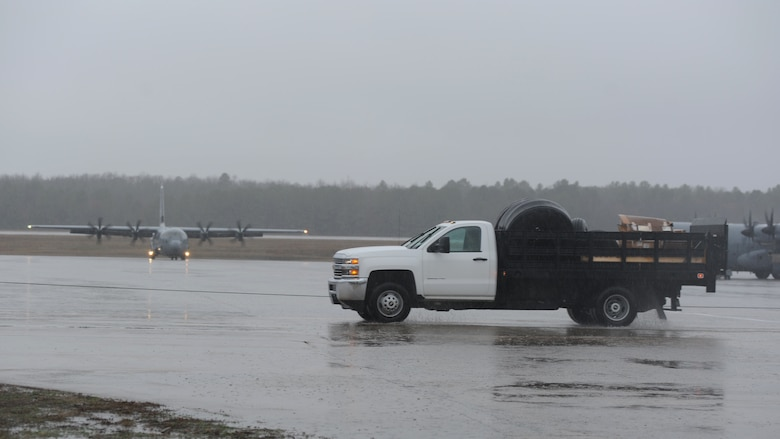A rectangle photo with a truck on a flightline with an aircraft.