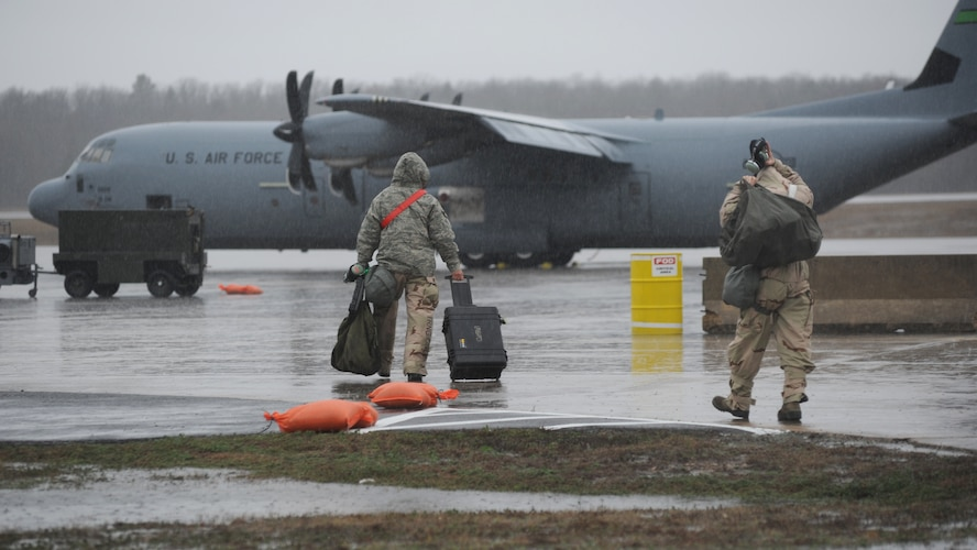Two males are pictured walking toward an aircraft in the rain.