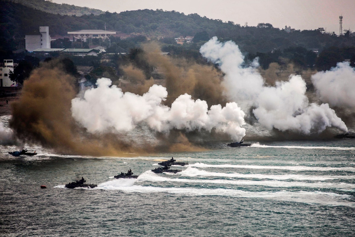 Amphibious vehicles travel in water toward a beach as white and brown smoke wafts in the background.
