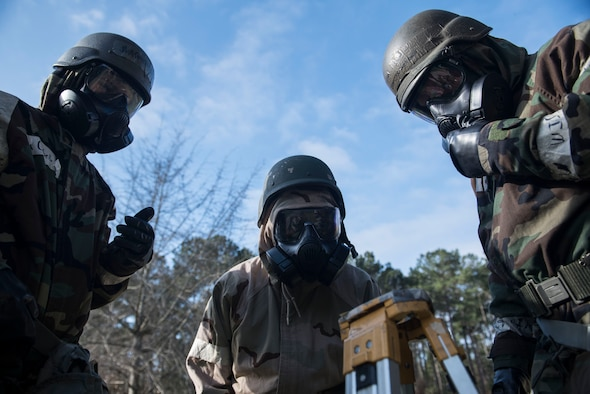 U.S. Airmen look down at a piece of M8 chemical detection paper at Shaw Air Force Base, S.C., Feb. 15, 2018.