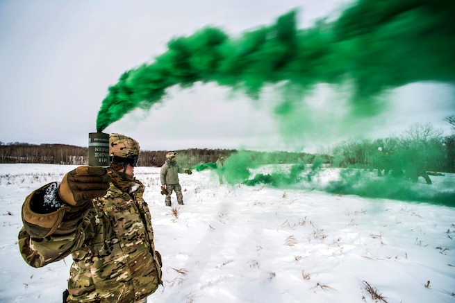 Green smoke streams from a can an airman holds up while standing in snowfield.