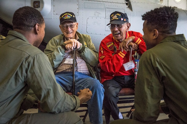 Two veterans lean on canes while sitting and laughing with two Marines.