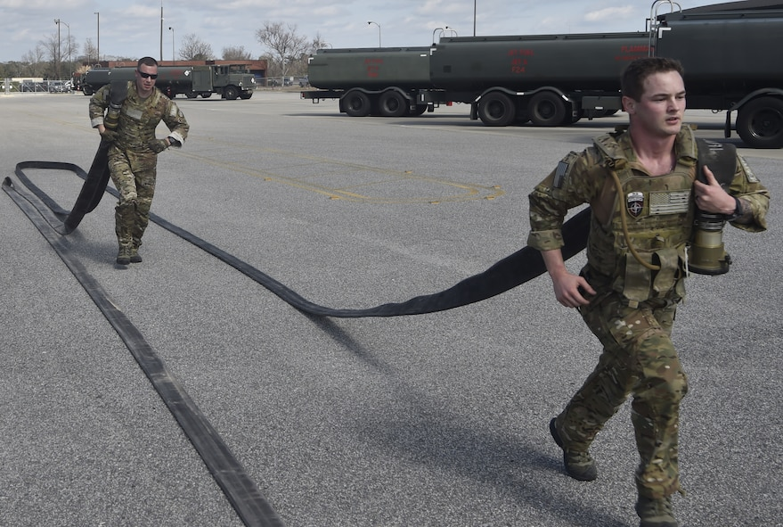 Tech. Sgt. Nicholas T. Piper, left, 628th Logistics Readiness Squadron Forward Area Refueling Point team chief and Senior Airman Christopher Stuebbe, right, 628th Logistics Readiness Squadron fuels distribution supervisor run with fuel hoses as part of a demonstration during a FARP team tryout Feb. 15, 2018.