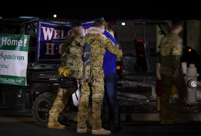 A member of the 66th Rescue Squadron is greeted by family after returning from deployment Feb. 8, 2018, at Nellis Air Force Base, Nevada. 66th RQS and 823rd MXS members were deployed for four months to support Operation Inherent Resolve. (U.S. Air Force photo by Airman 1st Class Andrew D. Sarver)