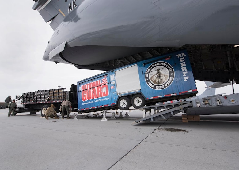 Airmen from the 176th Wing, Alaska Air National Guard and Washington Army Guardsmen load a cargo trailer onto a C-17 Globemaster III February 20, 2018 at Fairchild Air Force Base, Wash. Nearly 250 Air and Army Guardsmen from Alaska, Colorado, Connecticut, Indiana, South Dakota, Utah, and Washington are slated to participate in Exercise Arctic Eagle 2018 in Valdez, Alaska through the end of February. Arctic Eagle is a scenario-based exercise in which Guardsmen will conduct Homeland Response Force (HRF) and Chemical, Biological, Radiological, Nuclear and High Yield Explosive (CBRNE) Enhanced Response Force Package (CERFP) operations in a cold weather environment. (U.S. Air National Guard photo by Staff Sgt. Rose M. Lust/Released)