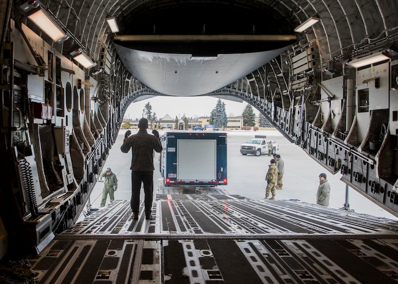 A loadmaster from the 176th Wing, Alaska Air National Guard, helps guide a cargo trailer onto a C-17 Globemaster III February 20, 2018 at Fairchild Air Force Base, Wash. Personnel, equipment, and vehicles are scheduled to be transported to Valdez, Alaska for use in Exercise Arctic Eagle February 20-27. (U.S. Air National Guard photo by Staff Sgt. Rose M. Lust/Released)