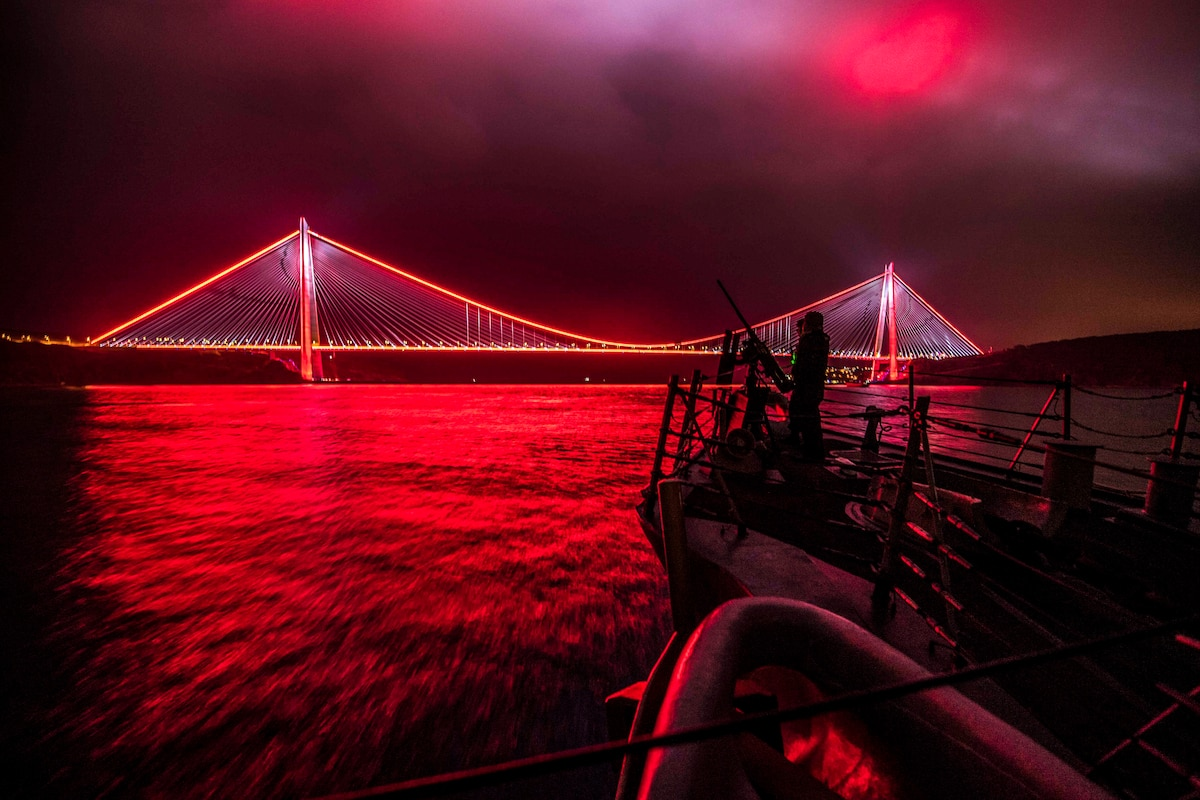 Sailors man a gun on a ship and look out over a suspension bridge illuminated in red light at night illuminated in red light.