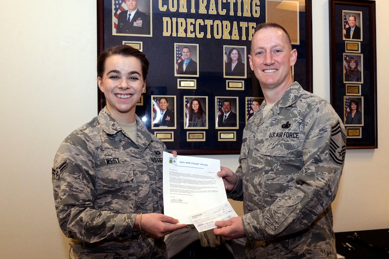 Airman 1st Class Allison West, Contracting Directorate, receives a $750 scholarship from Chief Master Sgt. Rulon Walker, representing the Chiefs' Group, at Hill Air Force Base, Utah, Feb. 15, 2018. (U.S. Air Force photo by Todd Cromar)