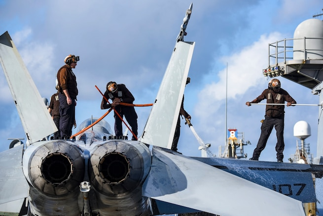 Four sailors stand atop an aircraft and wash it using a hose and mops.