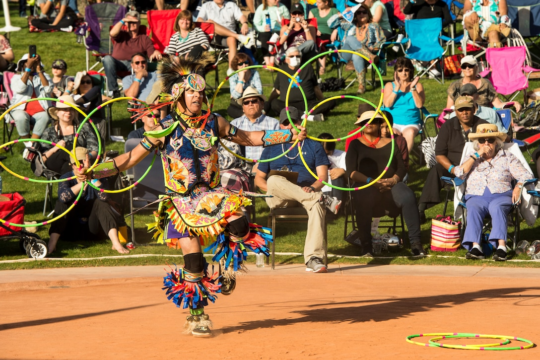 A man in Native American garb holds multiple hoops while dancing in front of a crowd outside on a lawn.