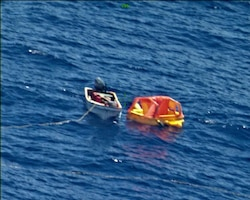 """CHUUK ATOLL, Federated States of Micronesia (Feb. 20, 2018) Mariners maneuver a UNI-PAC II Search and Rescue (SAR) kit closer to their vessel. The SAR kit was deployed from a P8-A Poseidon aircraft assigned to the """"Fighting Tigers"""" of VP-8, and its use during the rescue of three fishermen in the South Pacific marked the first time it had successfully been deployed in a real world SAR operation."""
