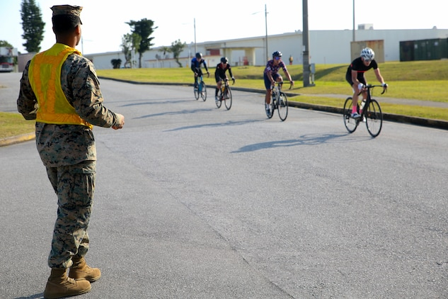 A Marine posts as a road guard during a bike race Feb. 18 aboard Camp Kinser, Okinawa, Japan. The race brought U.S. and local communities across Okinawa together to take part in friendly competition. About 130 racers participated in the first of four bike races held on Marine Corps bases in Okinawa throughout the year. (U.S. Marine Corps photo by Pfc. Nicole Rogge)