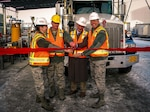 Four individuals cut a ceremonial ribbon for the opening of a new tank truck fueling station.