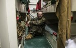 A Marine sits in his berth aboard an amphibious assault ship.