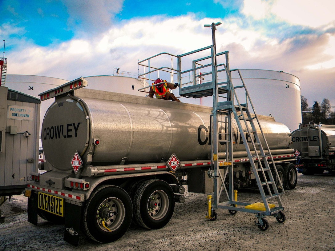 A quality assurance representative inspects a tank truck's compartments prior to loading.