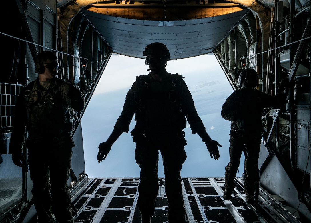 A U.S. Air Force 320th Special Tactics Squadron jumpmaster signals the start of military free fall operations from a U.S. Air Force 17th Special Operations Squadron MC-130J Commando II Sept. 21, 2017, at Kadena Air Base, Japan. The air drop capability provided by the 353rd Special Operations Group enables long-range rescue and rapid response to humanitarian or security crises. (U.S. Air Force photo by Capt. Jessica Tait)