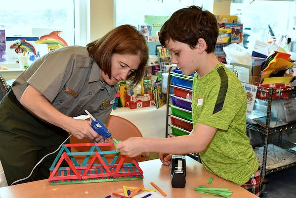 U.S. Army Corps of Engineers, Mobile District, Natural Resources Program Manager Amy Cobb-Williams works with a child at the University of South Alabama Children's & Women's Hospital, Feb. 20, to construct a bridge out of Popsicle sticks. The event was part of the district's National Engineers Week outreach program to teach school-age children the importance of science, technology, engineering and math (STEM).
