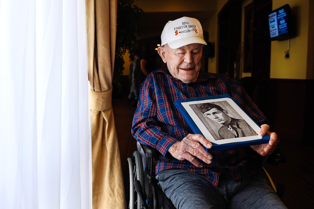 Retired Air Force Brig. Gen. Chuck Yeager looks at a photo of himself from the 1940s.