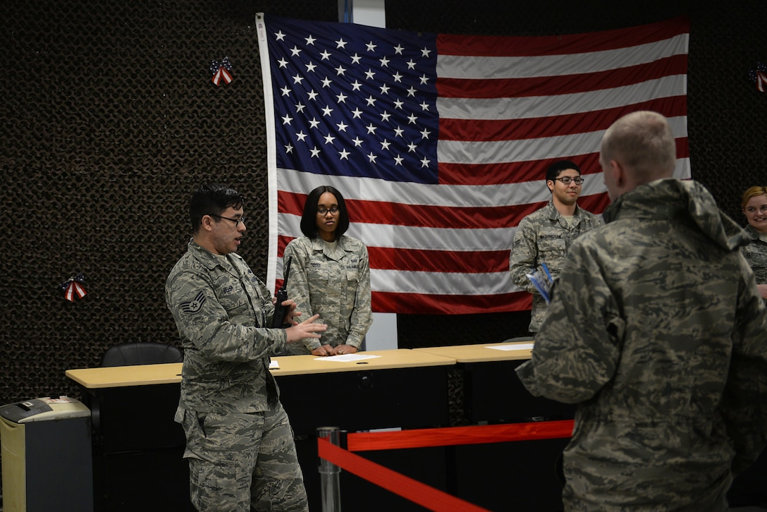 A staff sergeant in an Air Force Battle Uniform talks to a group of Airmen.