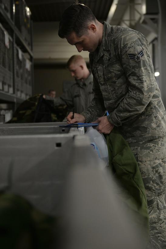 Three Airmen in Air Force Battle Uniforms grab MOPP gear out of bins.