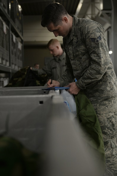 Three Airmen in Air Force Battle Uniforms grab MOPP gear out of bins.
