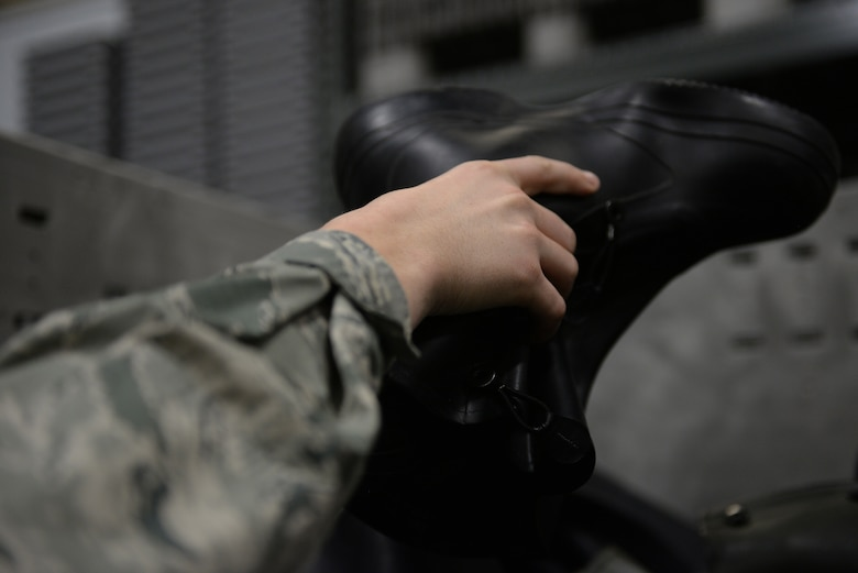 A hand with the Air Force Battle Uniform sleeve picks up a black boot.