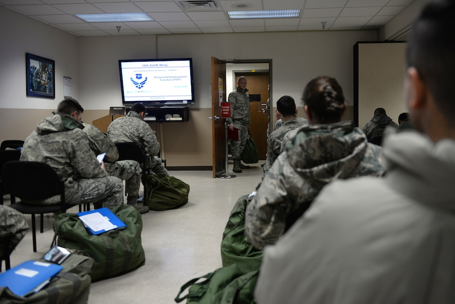 Airmen sit in a room with deployment bags on the ground next to them watching a screen.