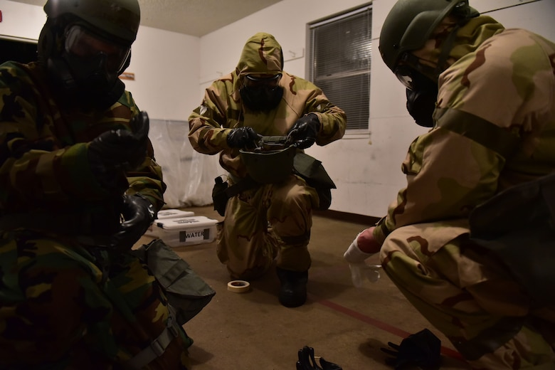 Three Airmen kneel and equip MOPP gear.