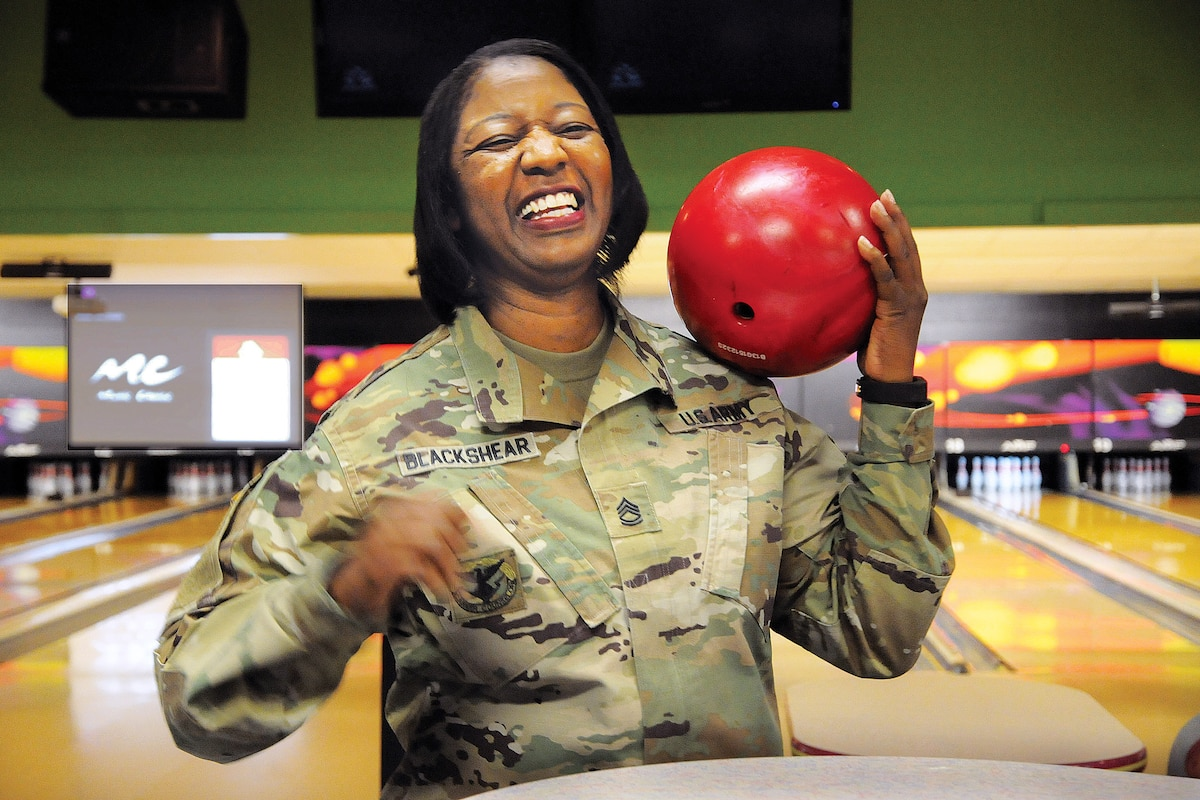 A soldier holds a bowling ball.