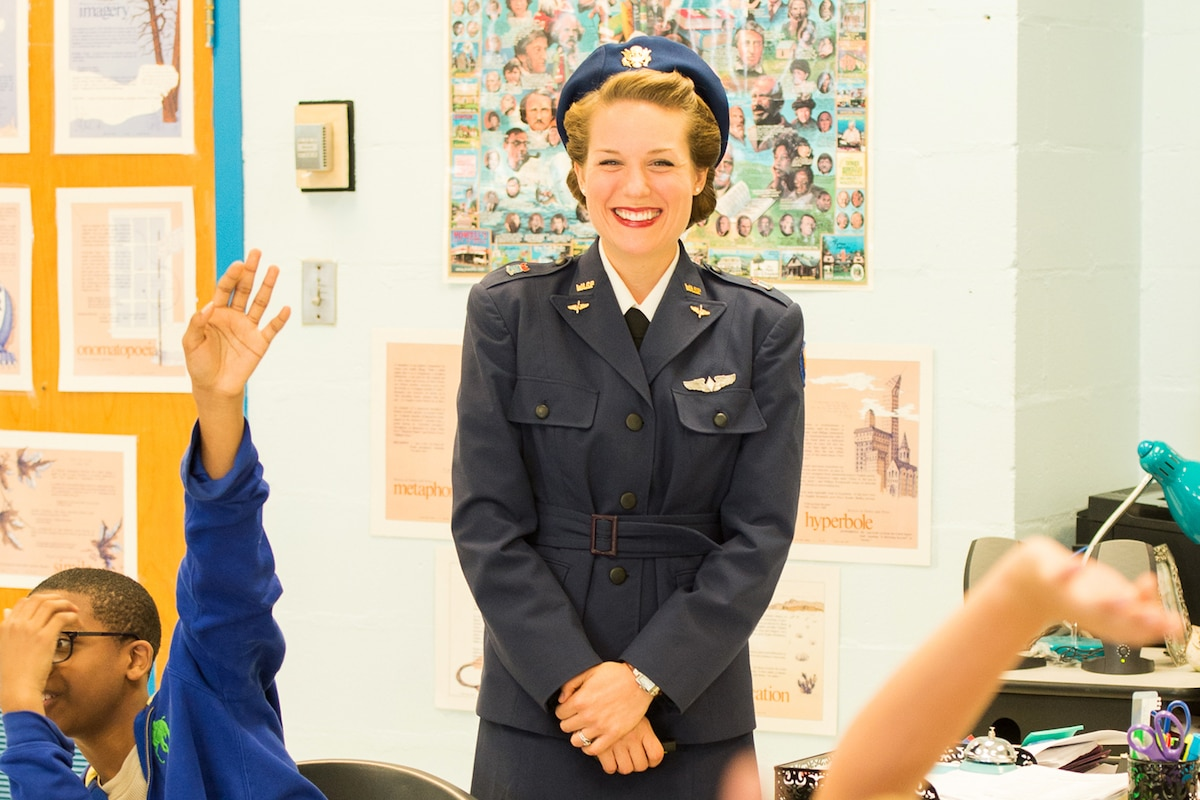 A woman dressed in a Women's Air Force Service Pilot uniform stands in front of a class.