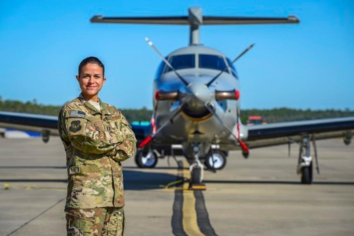 An airman poses next to a plane.