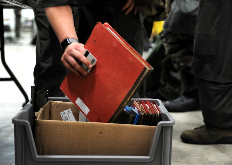 A photo with a red folding being placed into a grey container with other folders.