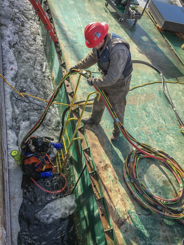 man assists diver entering icy lock for repairs