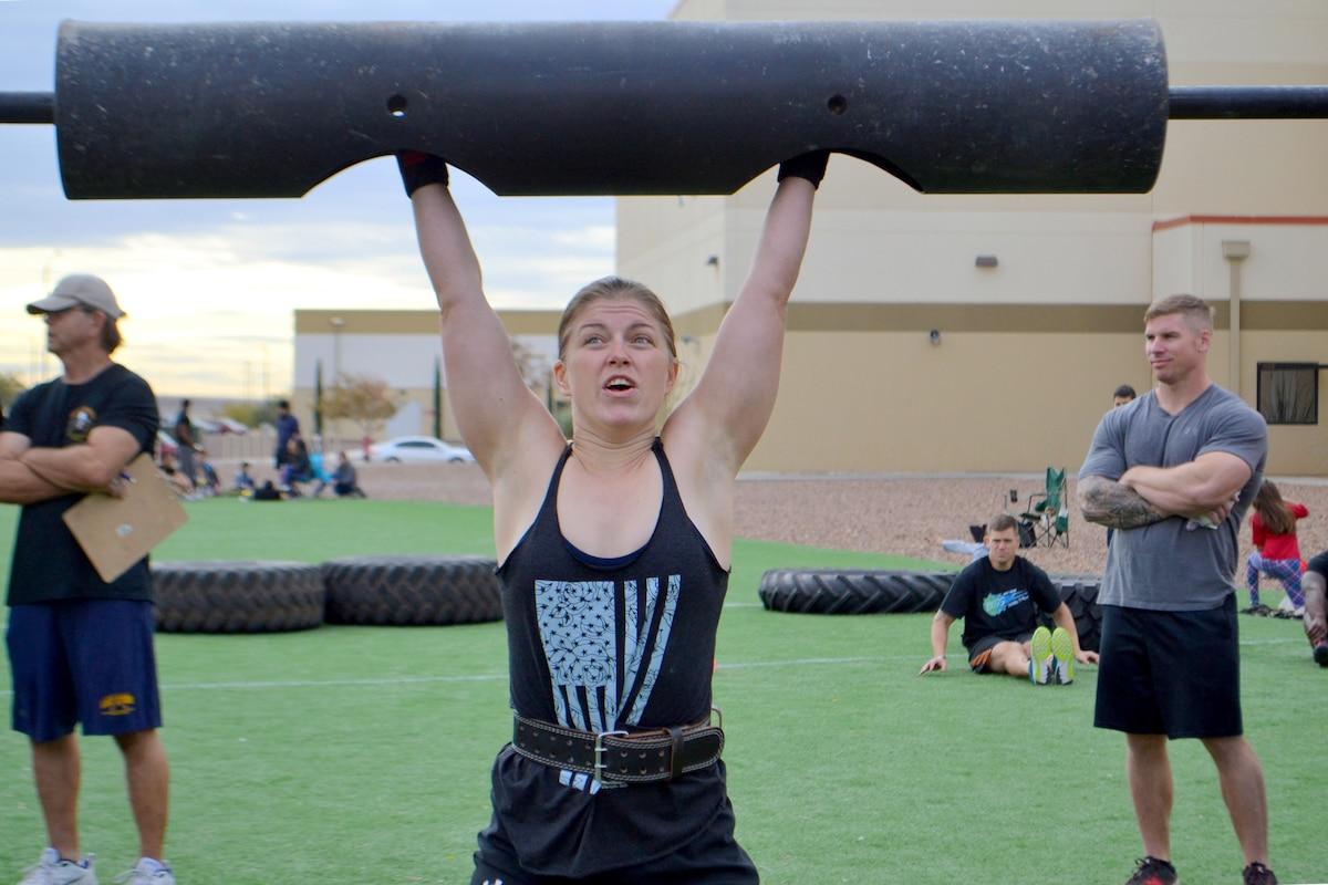 A women lifts weights over her head.