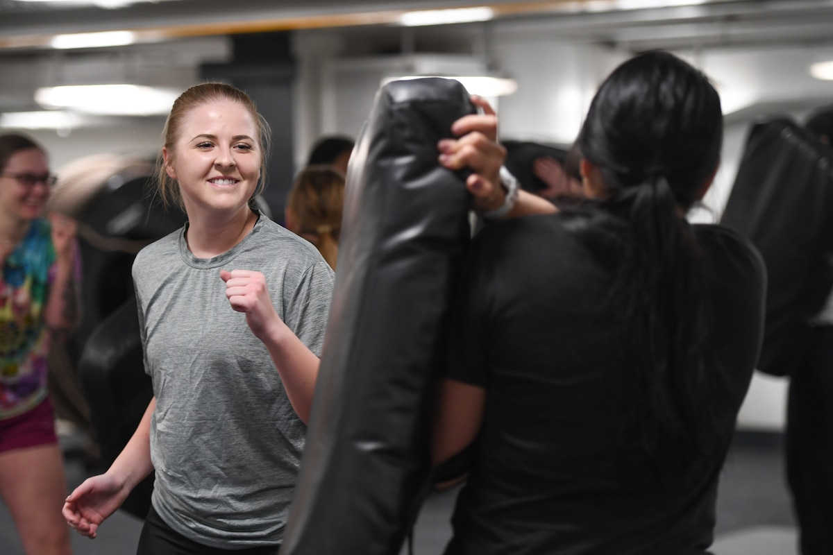 A woman lifts her fist while hitting a bag.