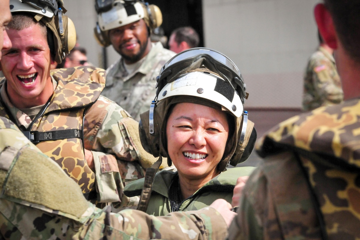 A soldier laughs with other soldiers.