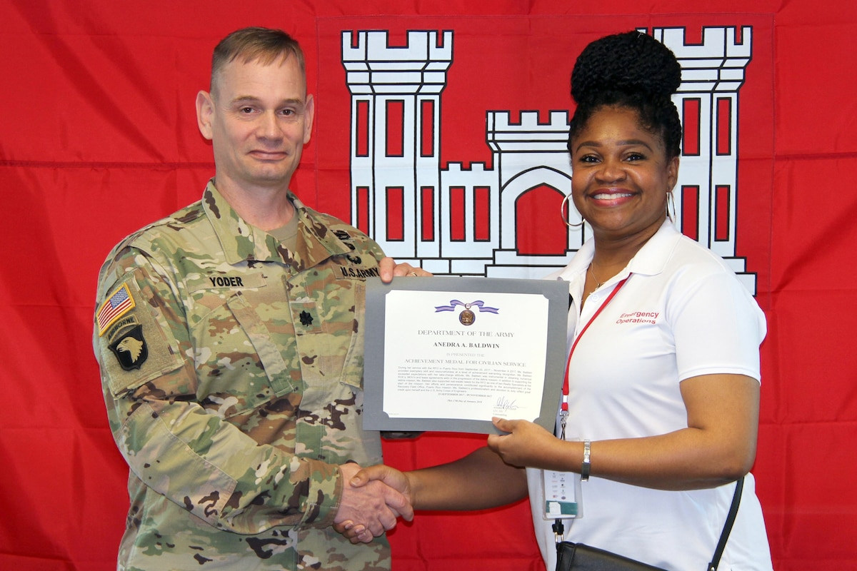 An army colonel hands a certificate to a person and shakes her hand.
