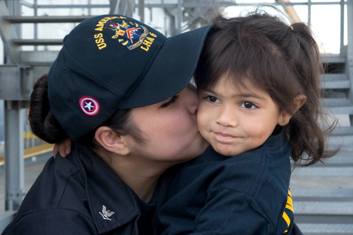 A sailor kisses a child on the cheek.