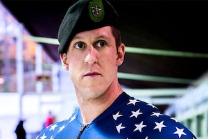 A soldier wears a Green Beret and an Olympic bobsledding uniform.