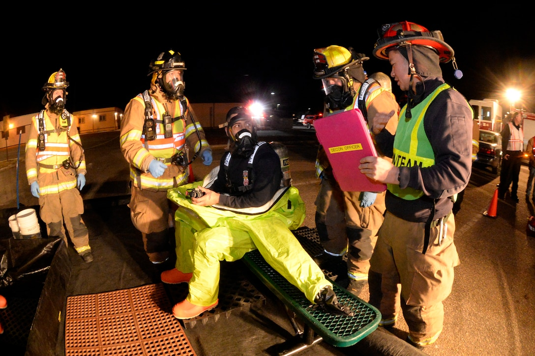 Fire Captain Joe Kuropatwa (center), decontamination officer, clarifies procedures with fellow firefighters during an emergency response exercise Jan. 30, 2018, at Hill Air Force Base, Utah. (U.S. Air Force photo by Todd Cromar)