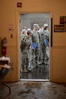 Airmen stand holding green bags through a doorway.