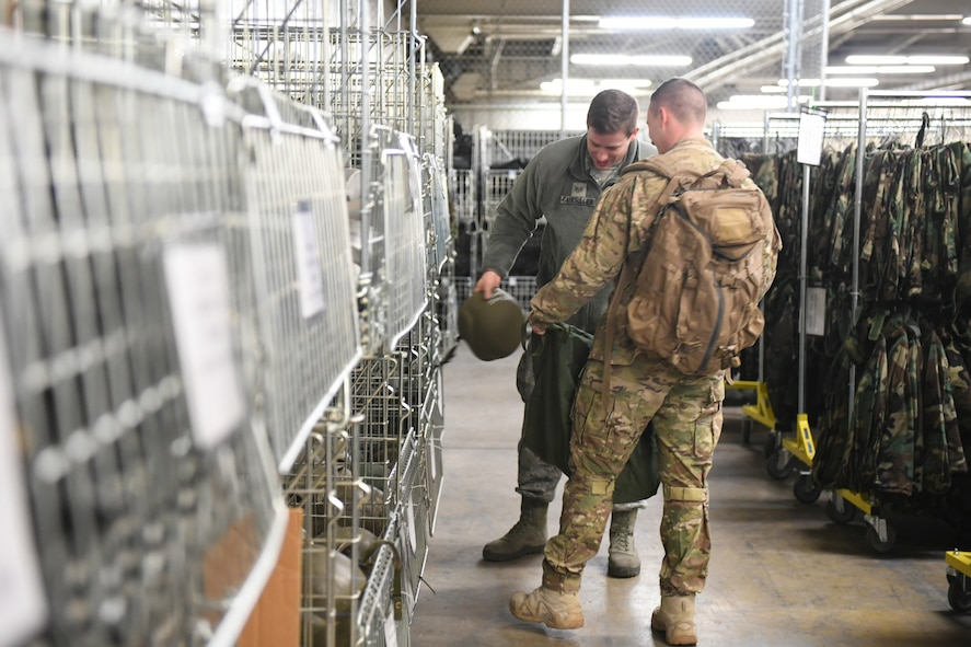 Staff Sgt. J.P. Caudrillier fills Senior Airman Patrick Schilling's mobility bag during a readiness exercise Jan. 29, 2018, at Hill Air Force Base, Utah. Airmen simulated the process of filling their mobility bags, weapon issue, and going through a pre-deployment function line. (U.S. Air Force photo by Cynthia Griggs)