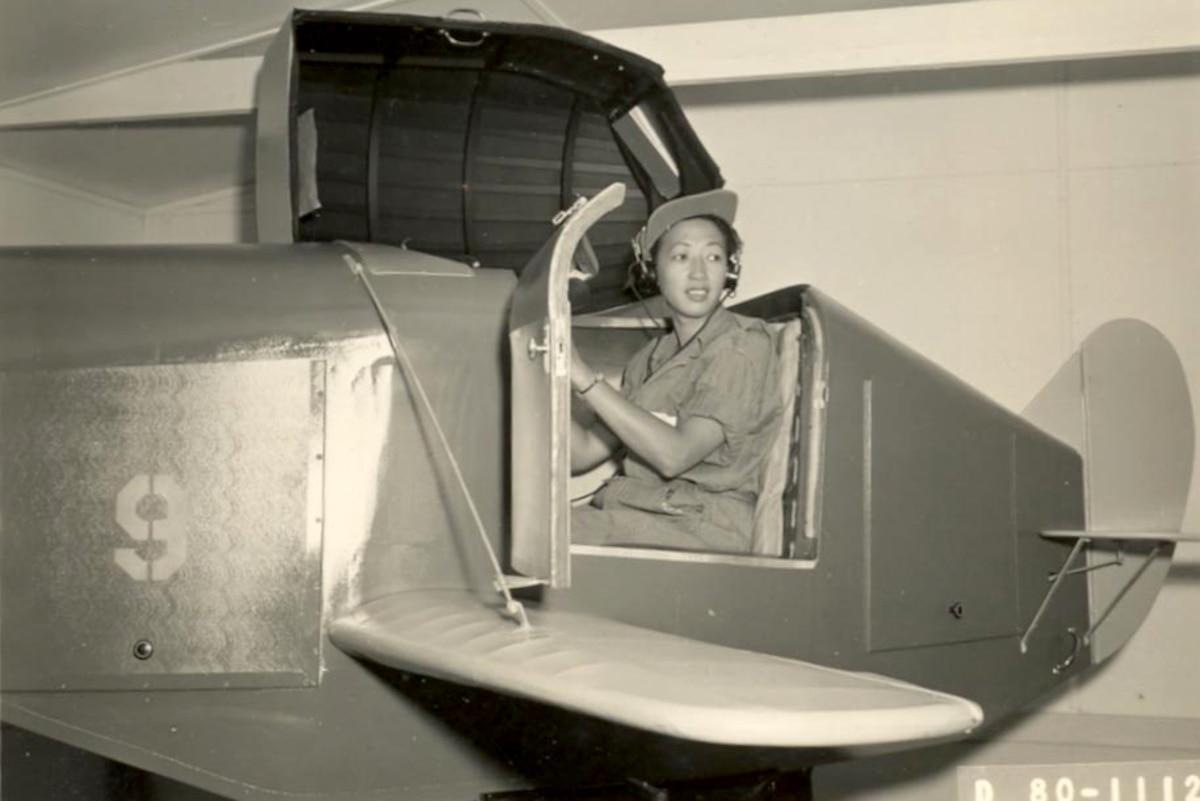 A historic photo of a member of the Women Airforce Service Pilots sits in an aircraft.