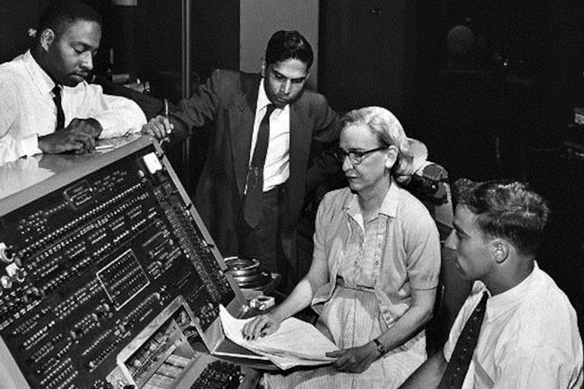 A woman programmer sits with others near a computer.
