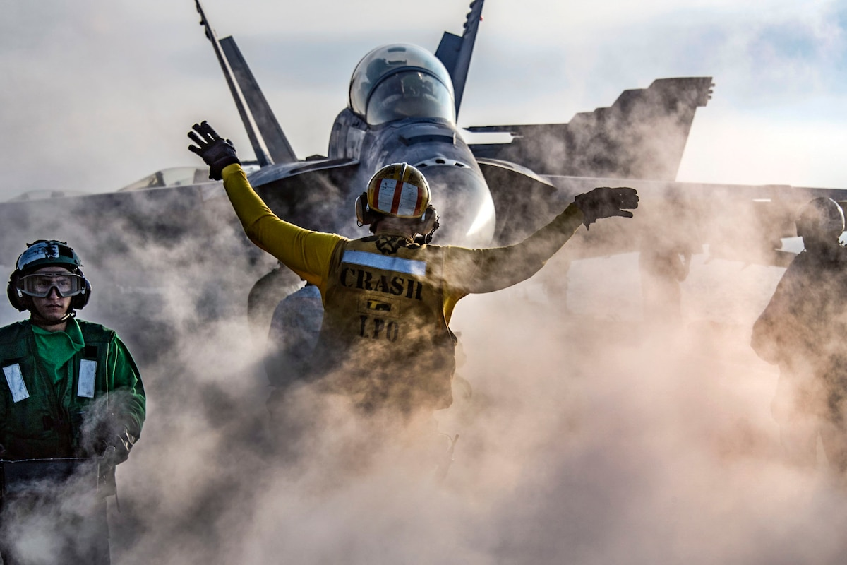 An sailor holds his arms out in front of an aircraft as smoke wafts upward around his waist.