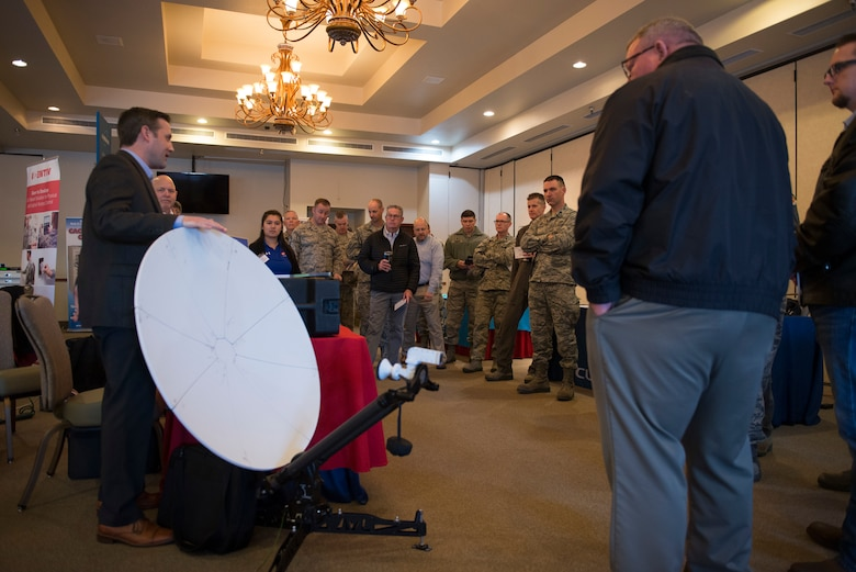 A technology company representative briefs 56th Fighter Wing leadership on new products during the 2018 Luke Tech Expo at Luke Air Force Base, Ariz., Feb. 22, 2018. The tech expo allowed wing leadership to view mission-centric technology exhibits from approximately 20 industry leaders in fields like telecommunications, cybersecurity, virtual reality and network management. (U.S. Air Force photo/Senior Airman Ridge Shan)